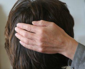 Een hand rust op de achterkant van een hoofd waardoor Reiki stroomt.