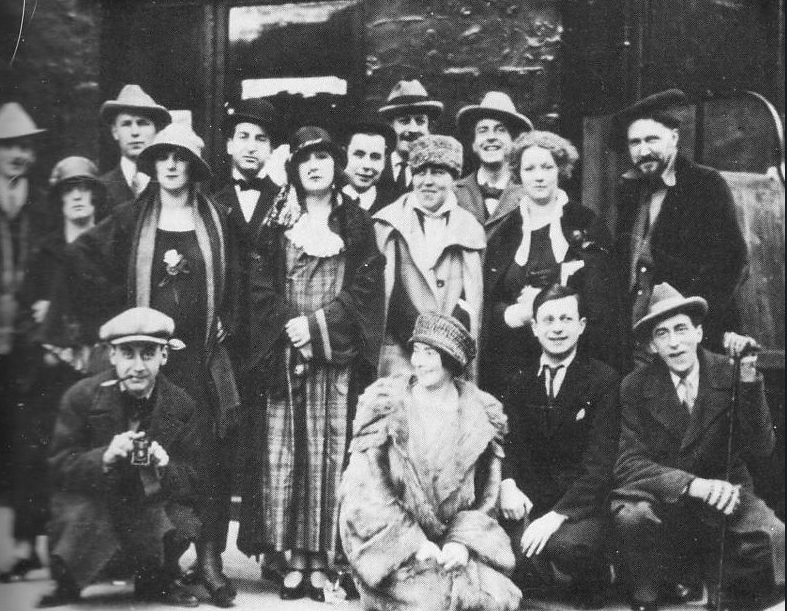 Members of the historical avant-garde gather in front of The Jockey in Paris in 1923. Front row: Man Ray, Mina Loy, Tristan Tzara, Jean Cocteau. Middle row: Kiki, Jane Heap, Margaret Anderson, Ezra Pound Top row: Bill Bird on the left, Hilaire Hiler and Curtiss Moffit on the right.