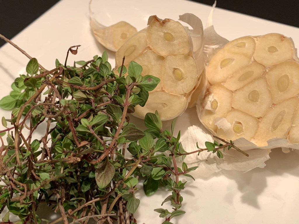 One head of garlic, cut in half and a small bunch of fresh thyme on a white plate.