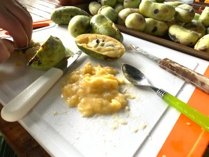 Several pawpaws with one being sliced open on a white and orange cutting board.