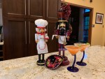 Two nutcrackers, a tiny sombrero and two orange colored cocktails in martini glasses.