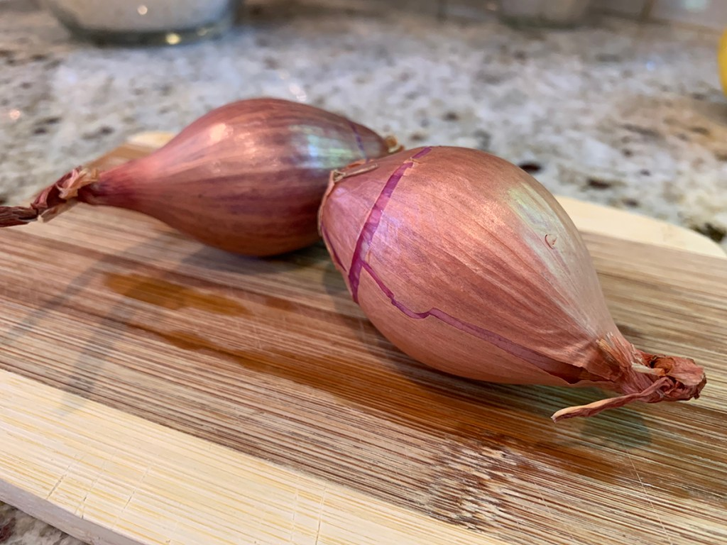 two shallots sitting on a bamboo cutting board
