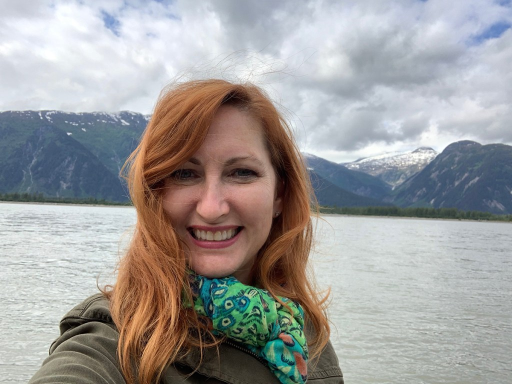 Girl with red hair, smiling with water and mountains behind her