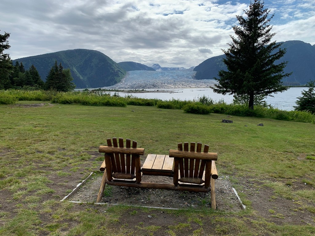 two adirondack chairs facing mountains on both sides of the hole in the wall glacier