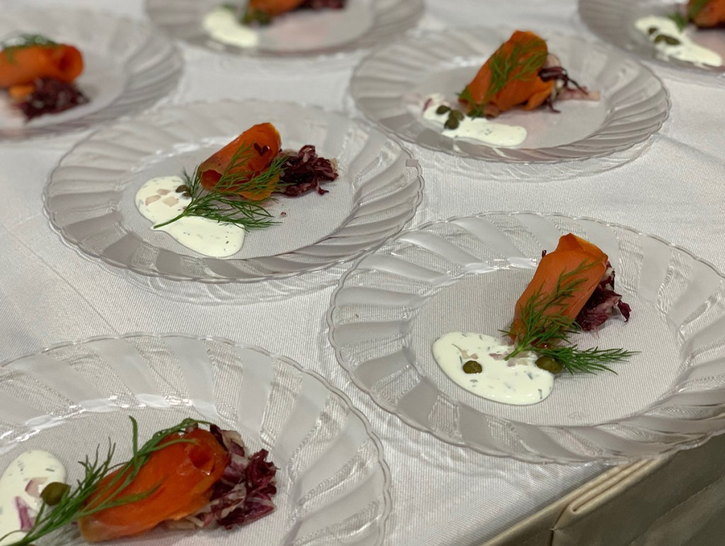 GravLox on clear plate on white table with sprig of dill and white sauce