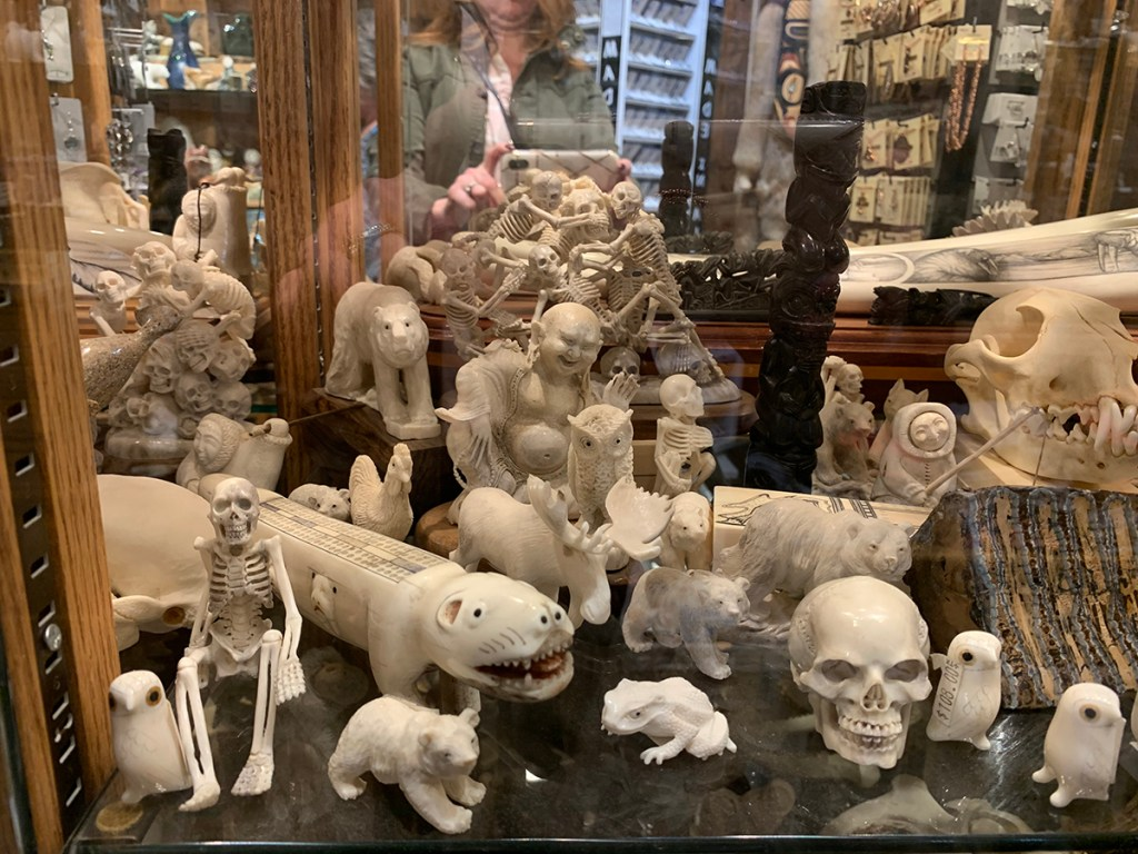 Multiple native bone carvings of skeletons, bears, owls, moose, frog and totem pole in glass case.