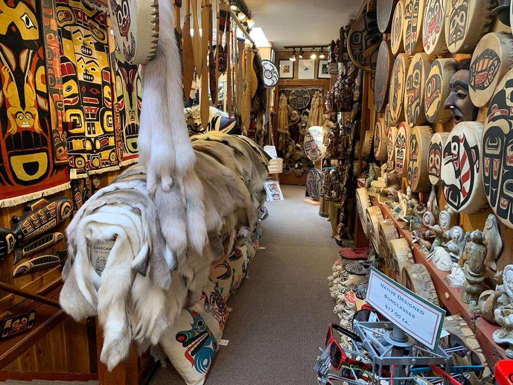 isle in native souvenir shop filled with furs, drums, printed pillows, carvings, rugs.