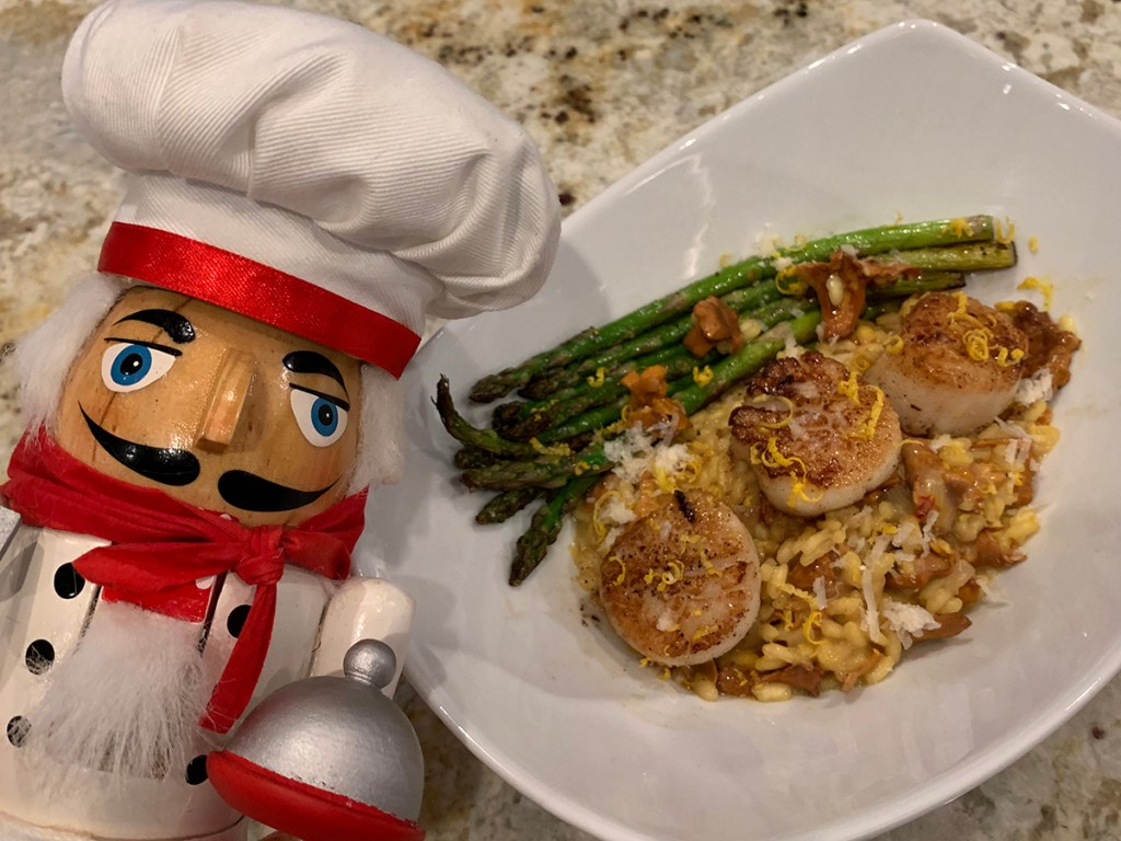 Seared scallops on a bed of a chanterelle and saffron risotto, sautéed asparagus in a white bowl with a nutcracker that looks like a chef