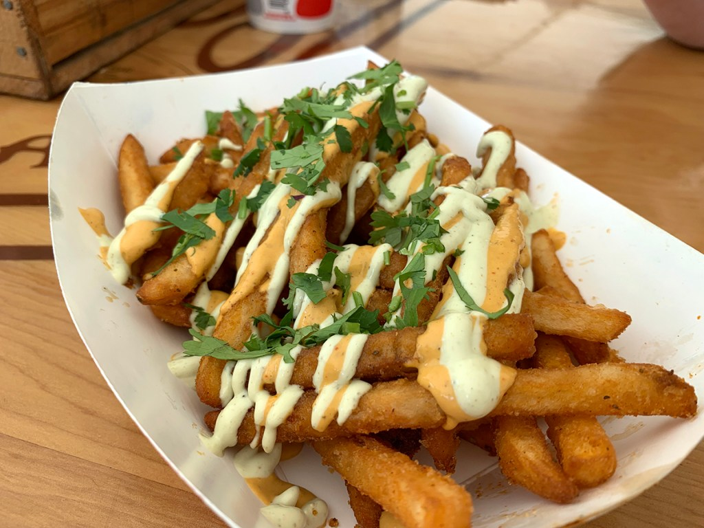 crispy french fries covered in spicy sauce and cilantro