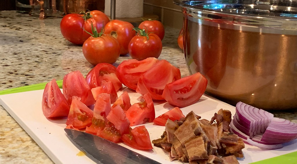 Several whole tomatoes in background with more cut up tomatoes in foreground on cutting board. Also has chopped cooked bacon on cutting board with knife. Brass bowl in background on the right.
