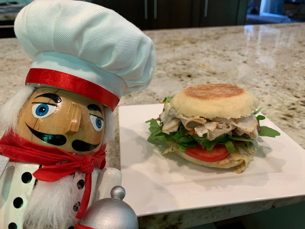 Turkey club sandwich made with homemade English muffin, turkey, bacon, tomato arugula and a mushroom & brie cheese. It's sitting on a white square plate and there's nutcracker who looks like a chef to the left.