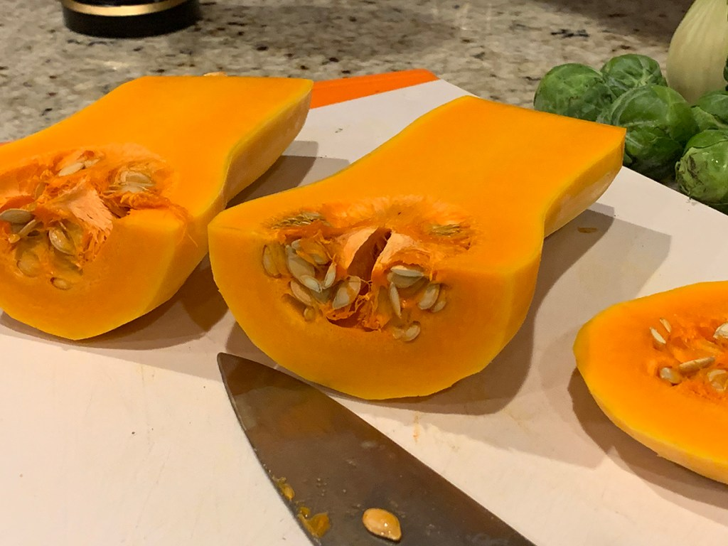butternut squasg peeled and halved. Seeds are still in and both halves are sitting on a white cutting board with a chef knife in front.