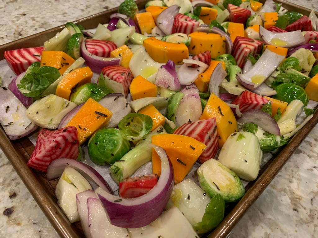 Raw mixed fall veggies ((butternut squash, red onions, brussles sprouts, fennel bulb and candy cane beet root) on a sheet pan ready for the oven.