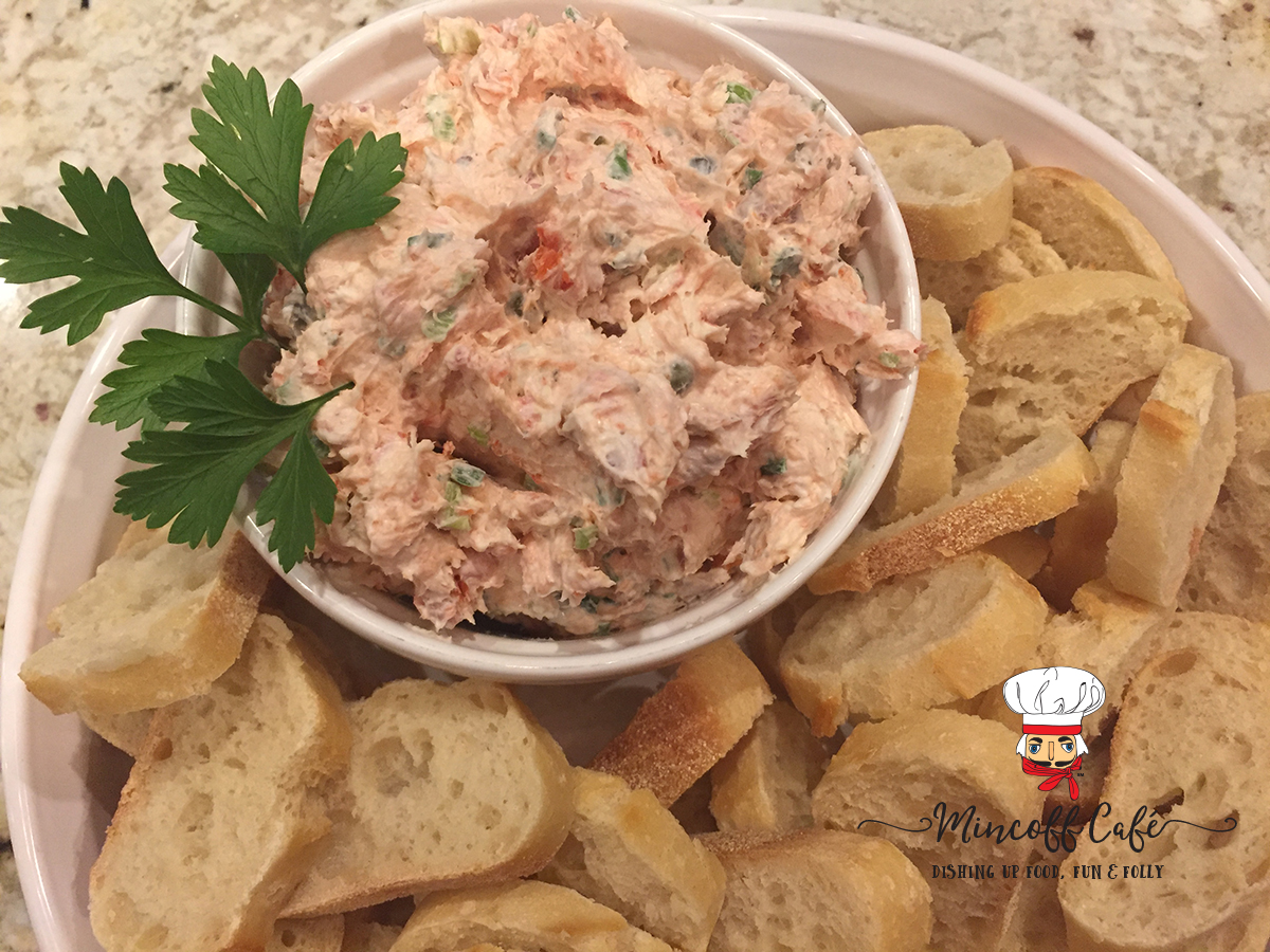 Smoked salmon dip in a white bowl, garnished with fresh parsley and inside another white bowl that has many sliced of french bread to spread it on.