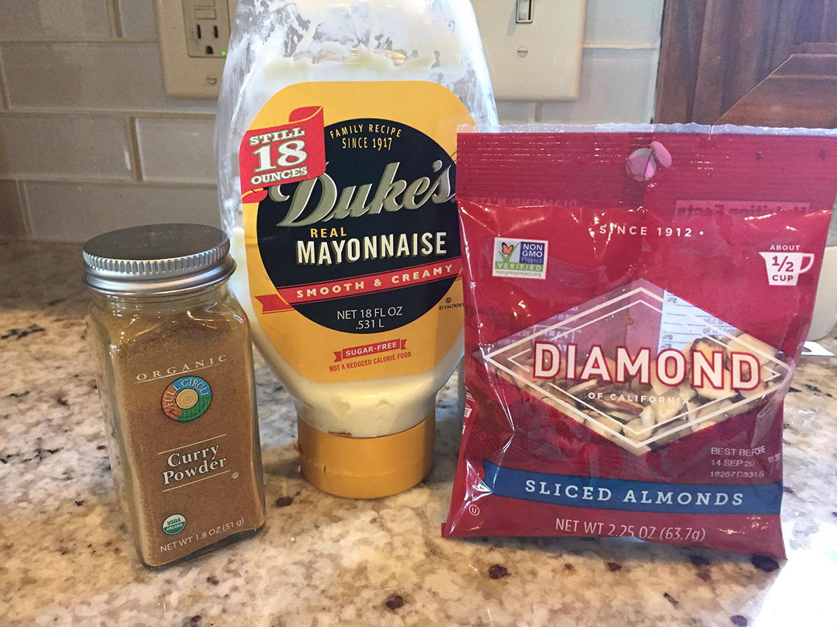 Jar of curry powder, bottle of Dukes Mayonnaise and a bag of Diamond brand sliced almonds.
