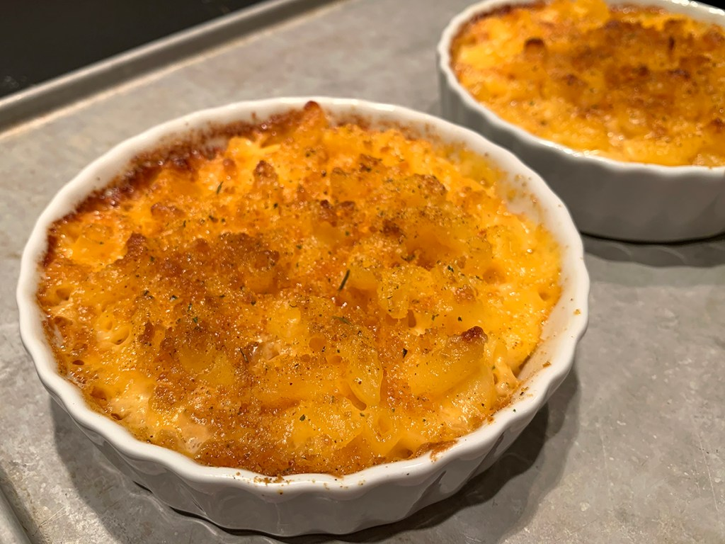 two round white ramekins with baked mac and cheese in them, sitting on a sheet pan.