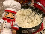 Mashed potatoes being made in a large sauce pan with a hand mixer. There's a nutcracker that looks like a chef in the foreground.