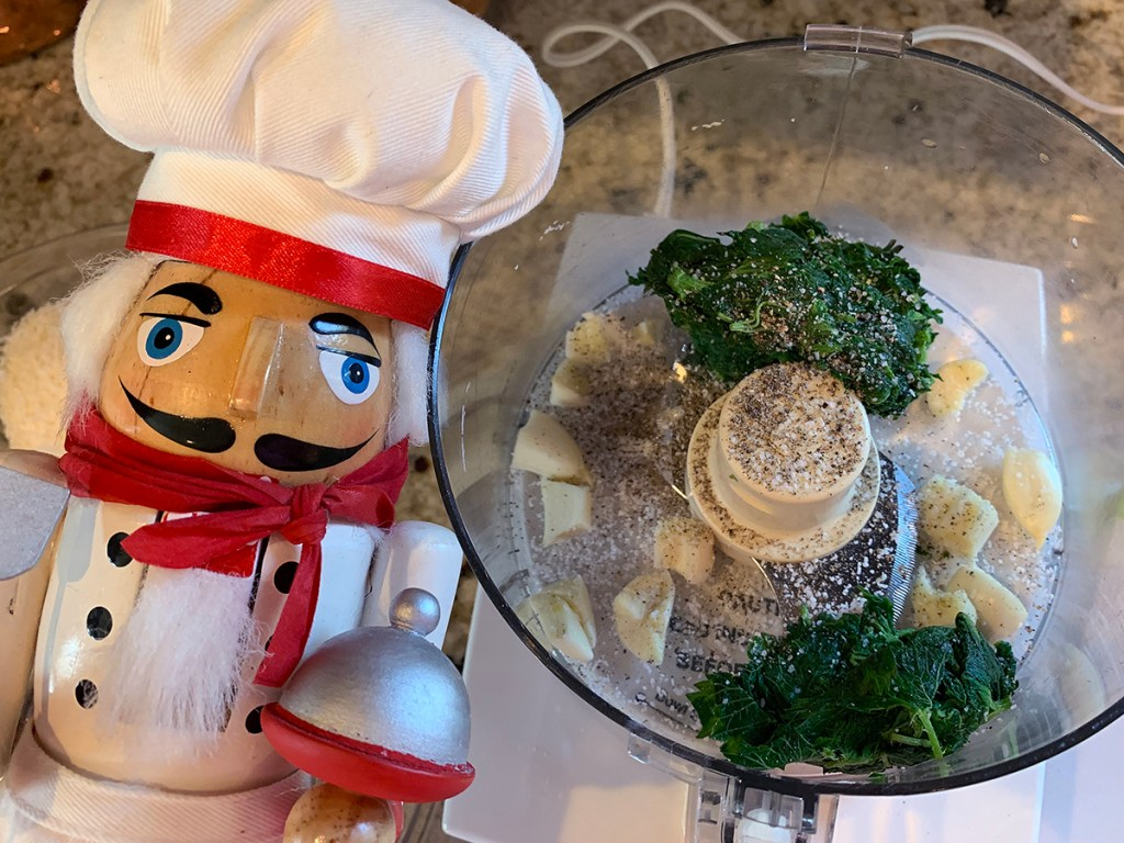 Stinging nettle leaves, garlic cloves, salt and pepper in a food processor. And a nutcracker who looks like a chef in the foreground.