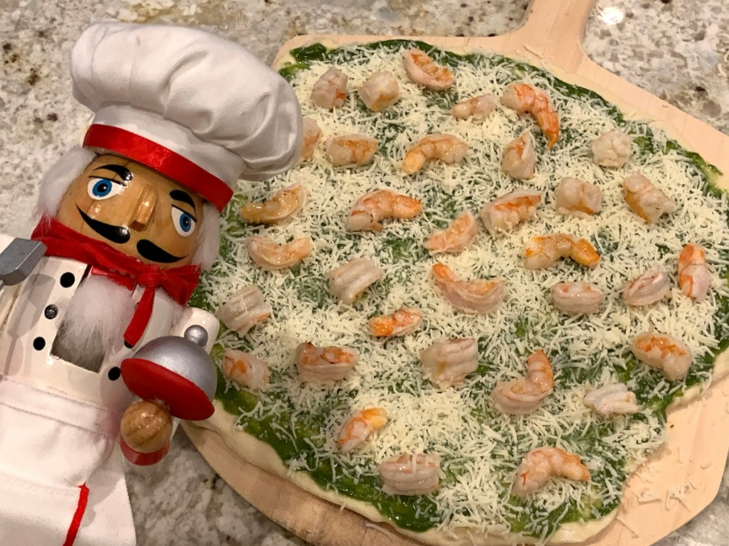Raw shrimp & nettle pesto pizza topped with fresh arugula and parmesan cheese on a wood pizza peel. There's a nutcracker who looks like a chef in the foreground.