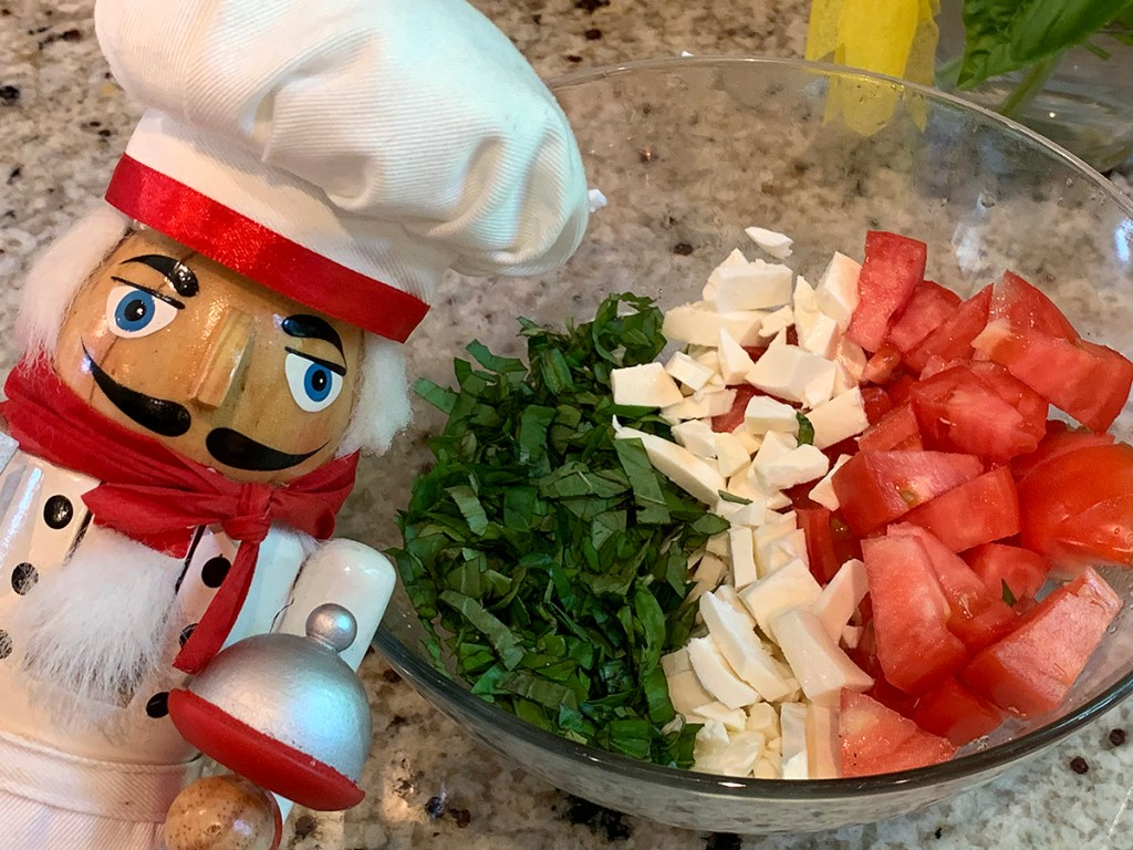 Basil, fresh mozzarella and tomatoes arranged in rows to represent the Italian flag. There's a nutcracker in the foreground who looks like a chef.
