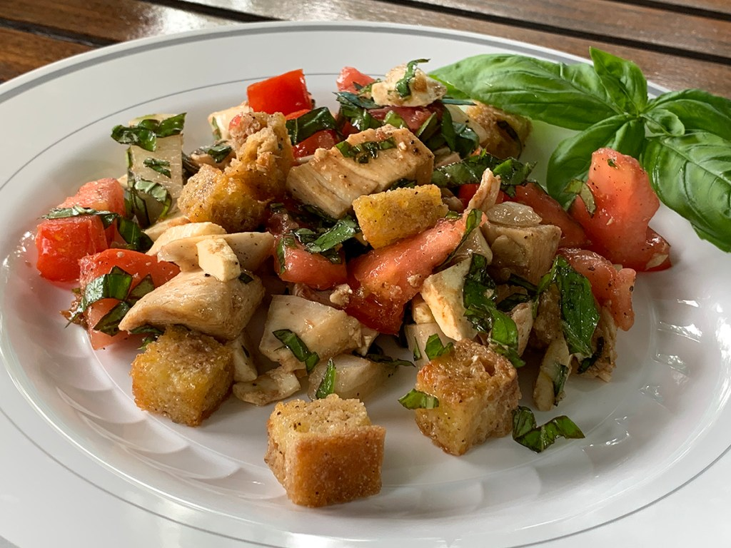 Chicken Panzanella (chicken, tomatoes, basil, onions and croutons) on a white plate.