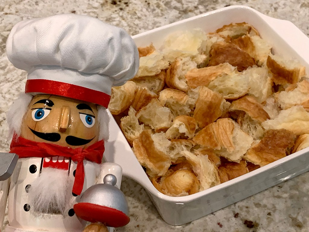 Large chunks of croissants in a square, white dish with a nutcracker who looks like a chef in the foreground.