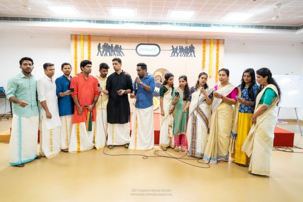 Group of Mindcurv members standing with microphones reciting words during Onam celebration