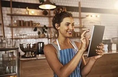 Young woman wearing a cooking apron using a tablet in her food business