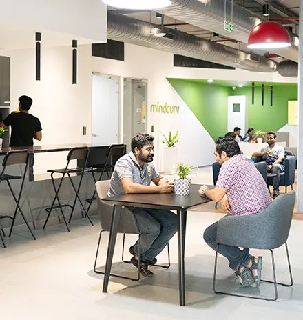 Members of Mindcurv team working on laptops in common are at Mindcurv's office at the World Trade centre in Cochin, India