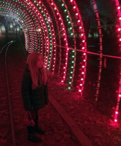 A young girl standing mezmorized inside a tunnel of dancing lights.