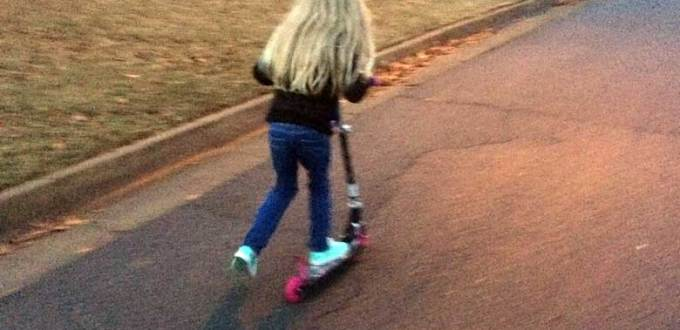 Blonde-haired girl riding a pink-wheeled scooter on a neighborhood street.