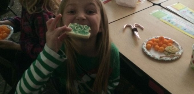 A girl acting silly while eating a sugar Christmas cookie.