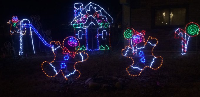 A vibrant Christmas light display featureing dancing gingerbread figures in front of a gingerbread house.