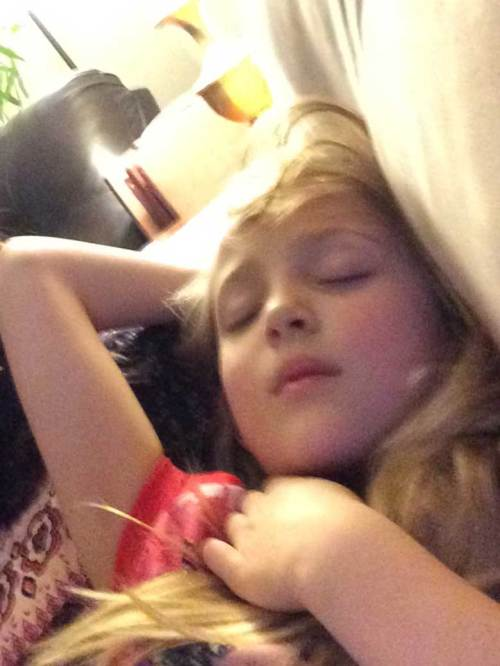 A blonde, female child asleep on the couch with rosy cheeks and her arm draped behind her head.