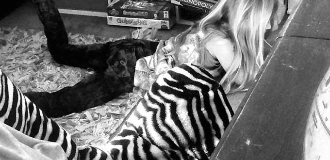 Black and white image of a girl reading while laying in the floor of her cluttered room with bookcases in the background.