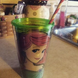 A fruit smoothie in a little mermaid cup with a candy-striped straw and a cookie jar in the background.