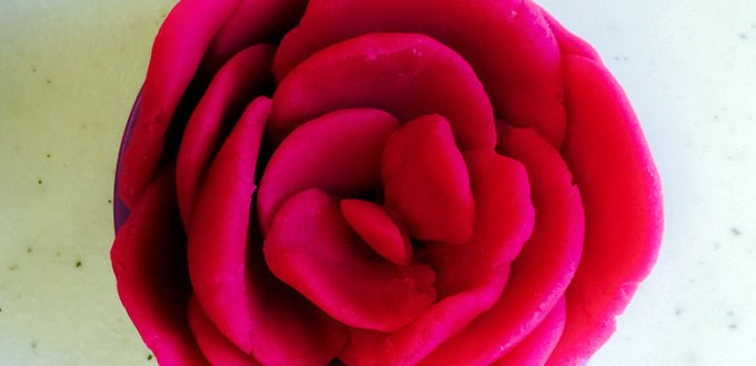 A rose made out of ruby red playdough.