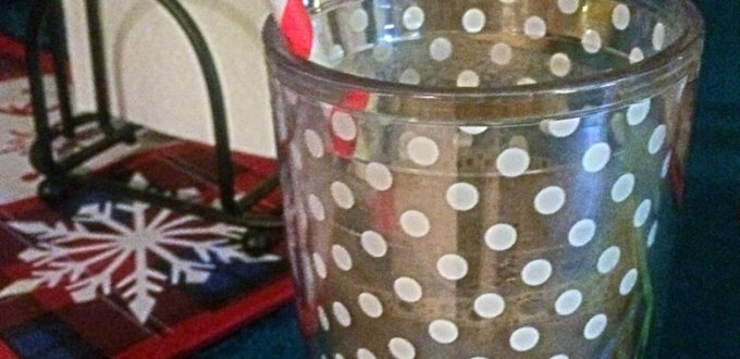Chocolate milk in a polka dot cup, with a candy-striped straw.