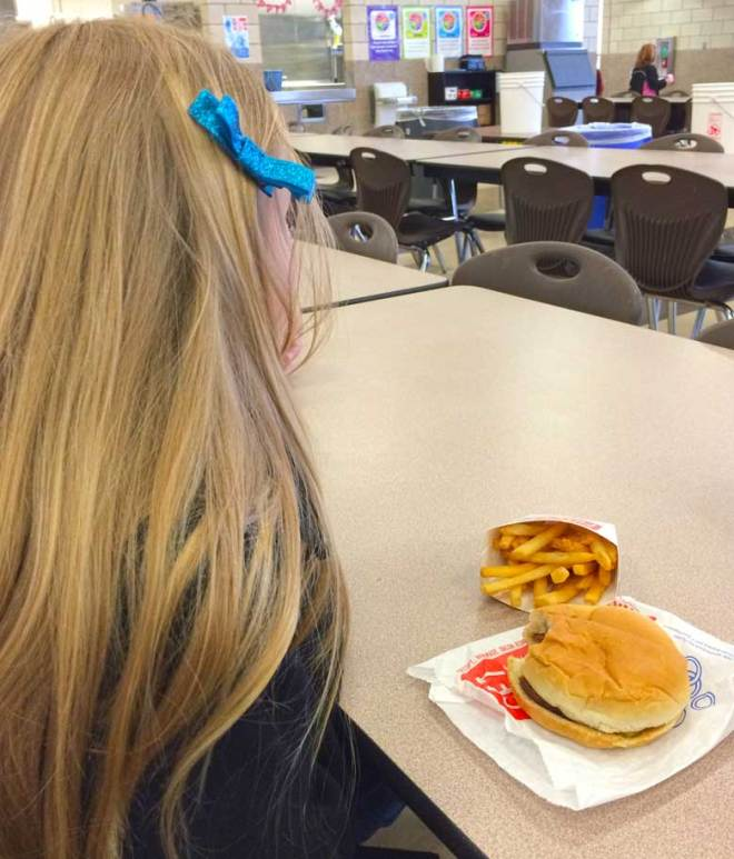 A blonde girl with a blue bow peering of into the distance while her food sits in front of her.