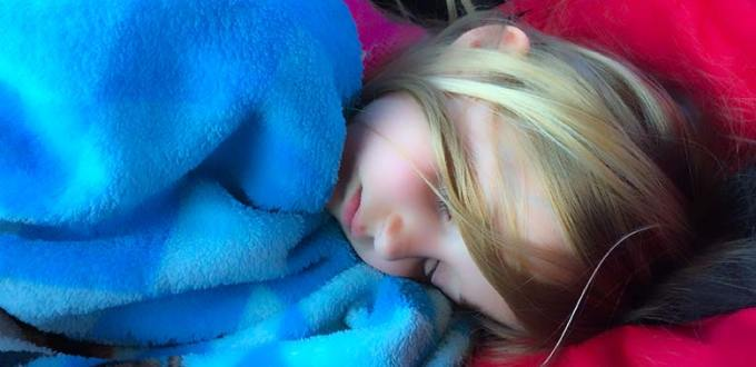 Blonde child snuggles up in a blue blanket, sleeping soundly.