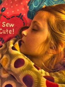 Young blonde girl with flushed cheeks asleep on a colorful blanket.