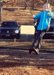 Blong girl in a blue sweater swinging and smiling, with a black and silver VW beetle in the background.