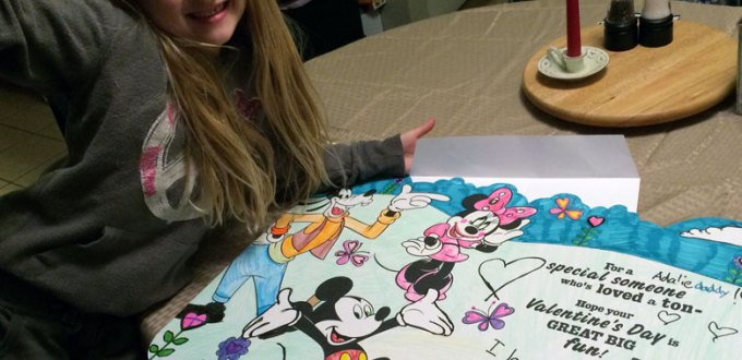 Blonde girl displaying giant Valentine's card with Mickey characters on a kitchen table.