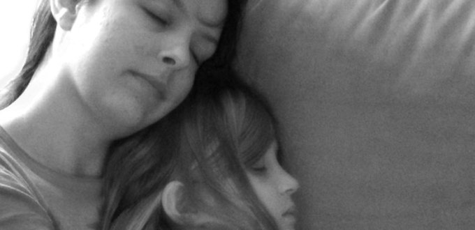 Mother and daughter sleeping soundly embracing on a couch. Picture in black and white.