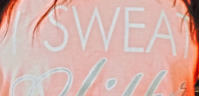 "A woman's salmon-colored Tshirt that reads ""I sweat glitter."""