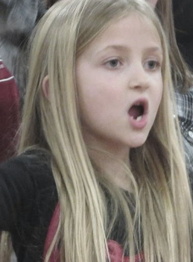 Blonde girl with mouth wide open singing.
