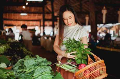 asian woman with basket and bundle of herb in market