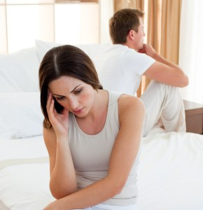 Photo of unhappy couple sitting in their bed | Online Marriage counseling in Texas | Couples therapy | Online marriage therapist in Texas
