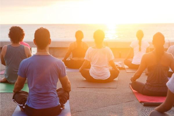 People meditating on the beach