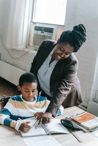 smiling black woman supporting little pupil during lesson in classroom